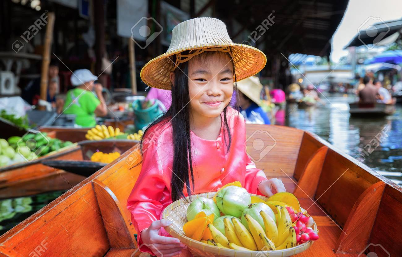 Chikd sit on the boat and hold the fruit basket in Traditional floating market , Thailand. Standard-Bild - 33982756