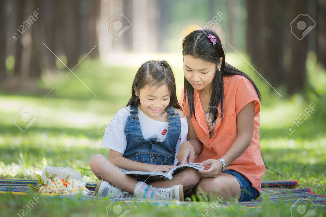 Mon and baby take a home work on the green nature and flower garden. Standard-Bild - 34619040