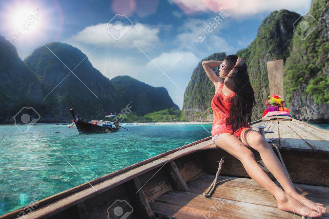 Asian lady relax on long tail boat at maya beach, Phi Phi island near Phuket in Thailand Standard-Bild - 38557471