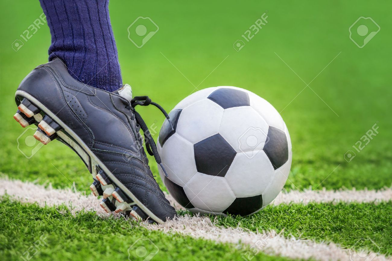 Shoot a soccer ball with his feet on the football field Standard-Bild - 42199020