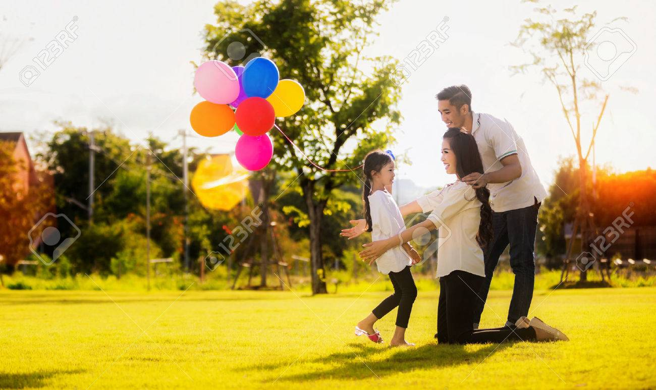 Daughter running to mother and father, She enjoyed the play balloons Standard-Bild - 72632746