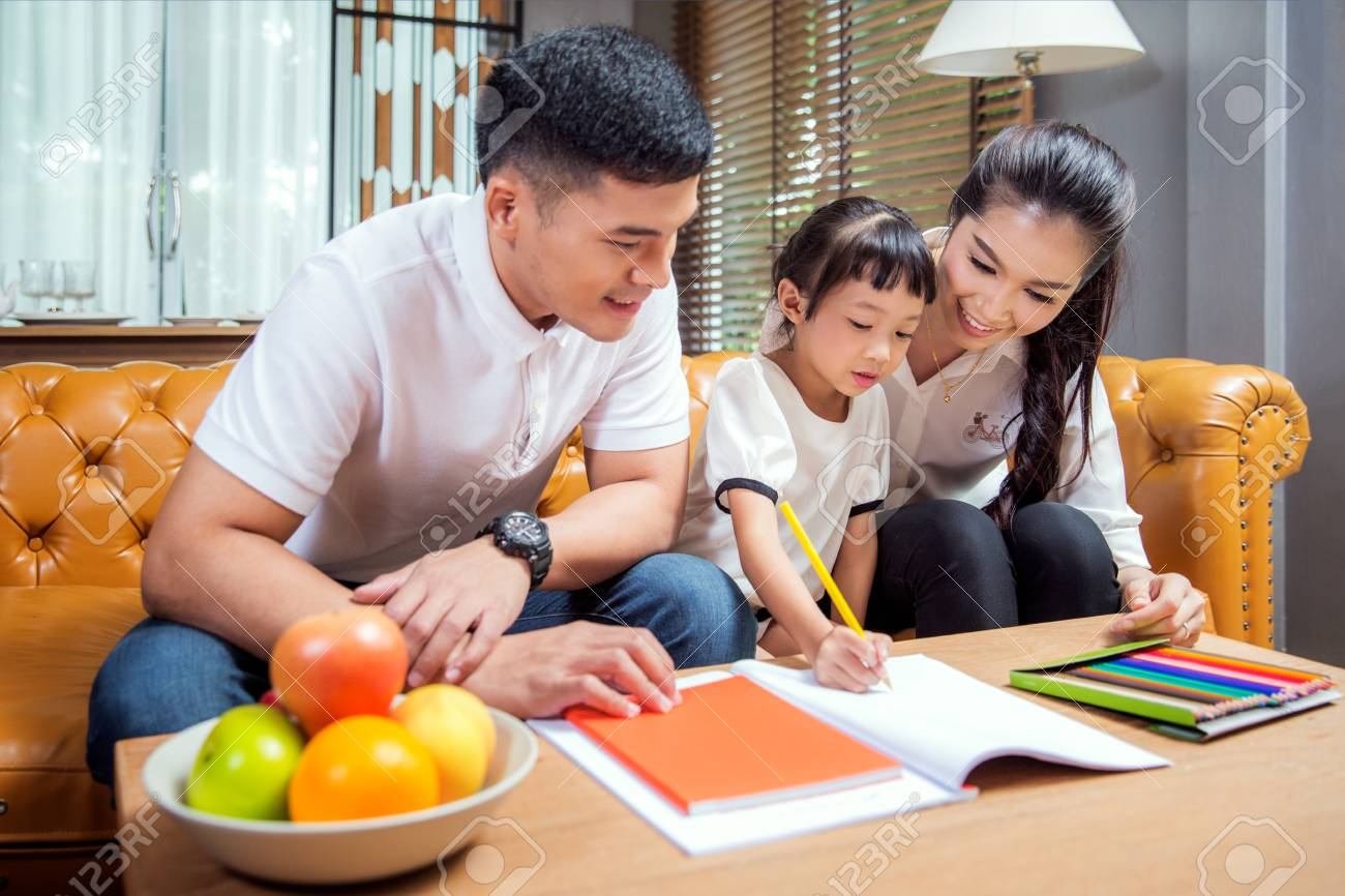Asian father, mother and daughter doing home work togather in living room, this immage can use for education, home and family concept - 98979123