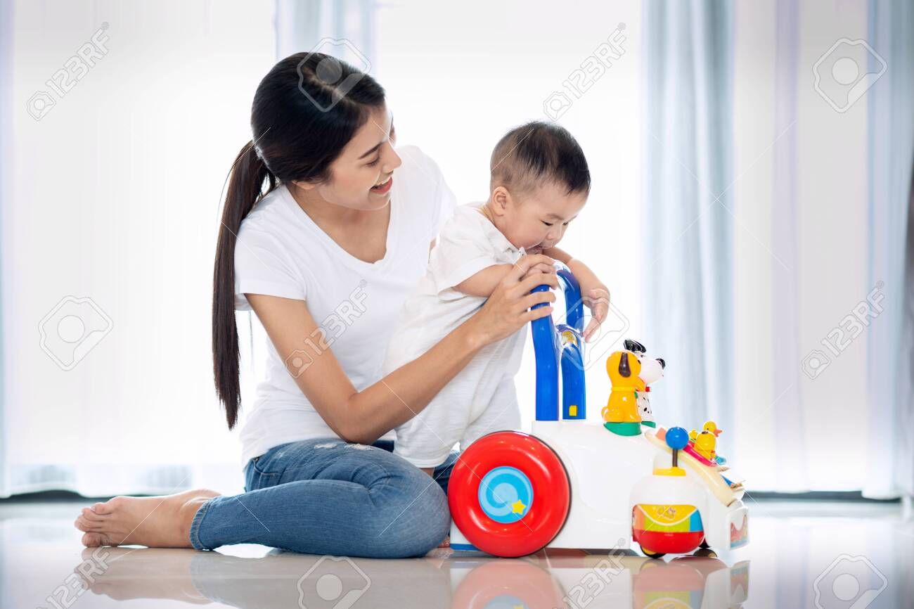 Asian mother training walking to her baby by walking toy - 132844887