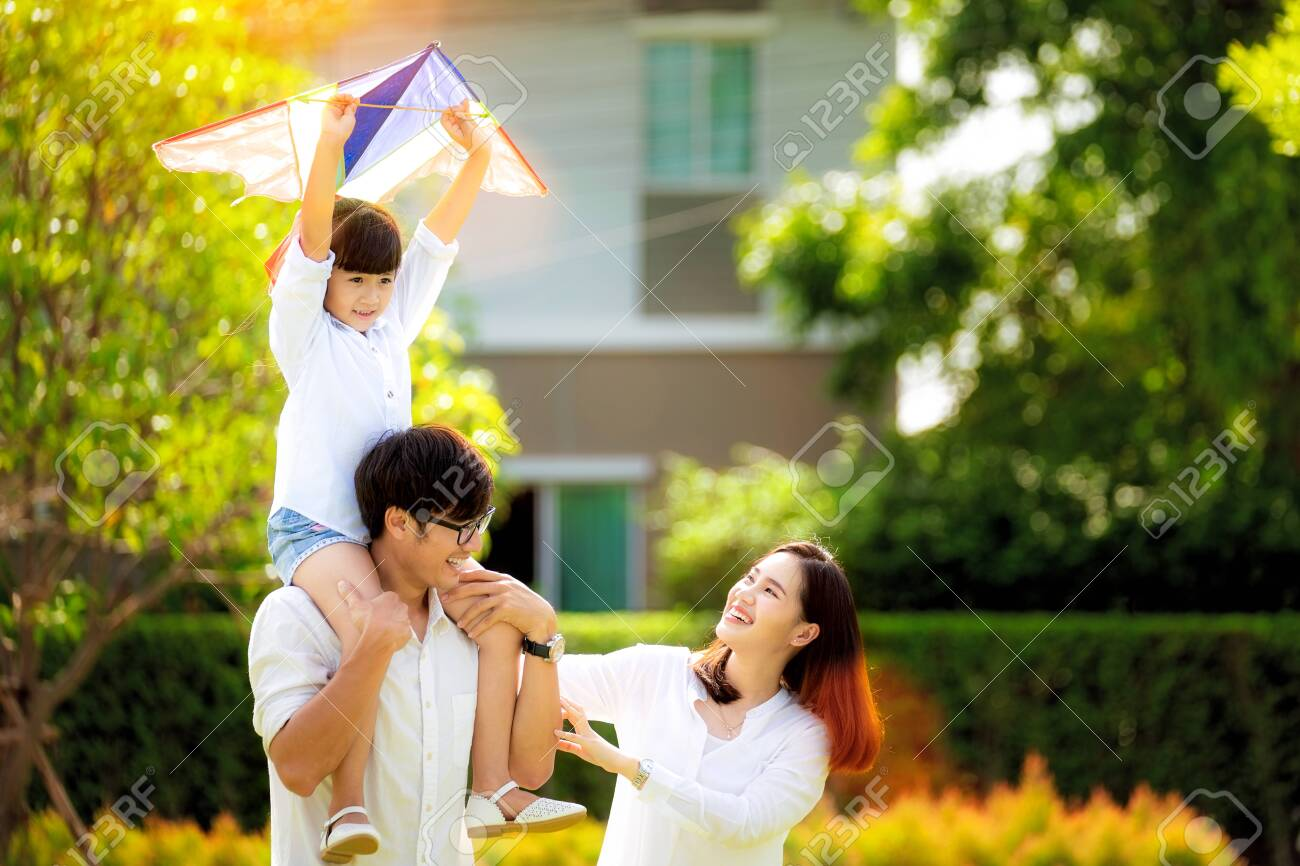 Asian family father, mother and daughter play a kite in the outdoor park in village near thay home, this image can use for family, relax, freedon, summer and travel concept - 132778420