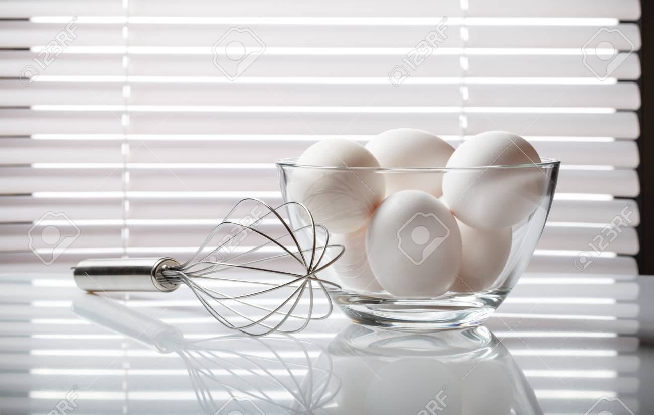 Wire Whisk And Glass Bowl Full Of Raw Eggs Over White Venetian ...