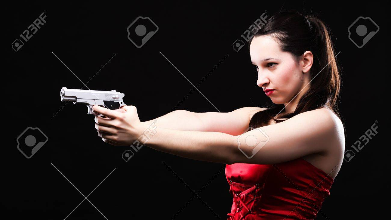 Sexy young woman in red with a gun on black background Stock Photo - 11344592