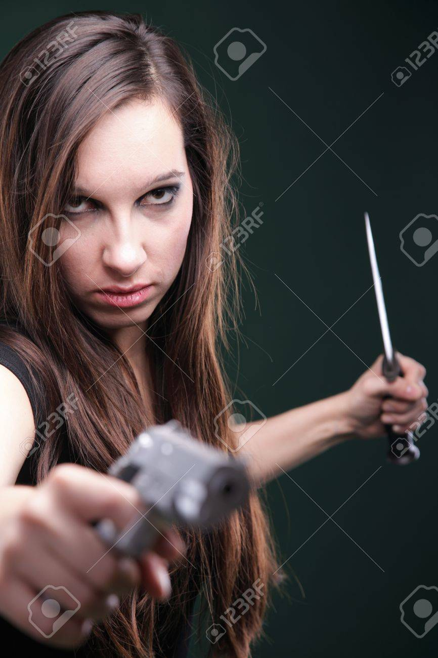 Sexy young woman in red with a gun, knife on green background Stock Photo - 11706327