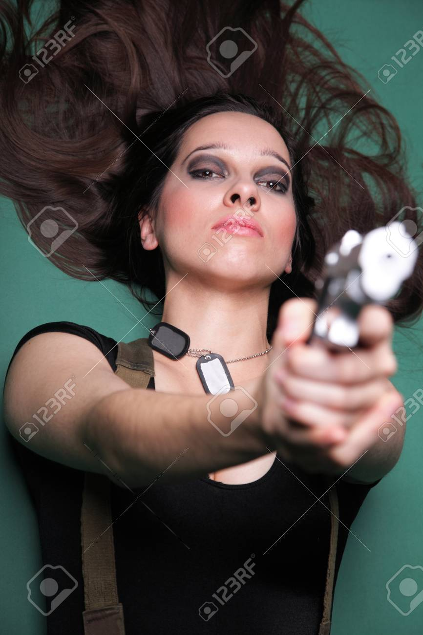 Sexy young woman in red with a gun, on green background Stock Photo - 13326889