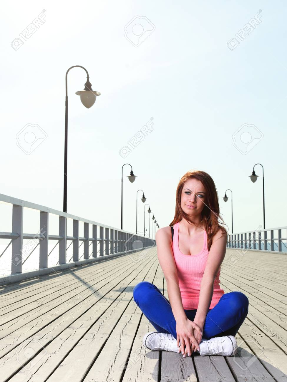 Attractive girl Young woman on pier Sits Crossed Legged Relaxing Old Wooden Pier Stock Photo - 15186451