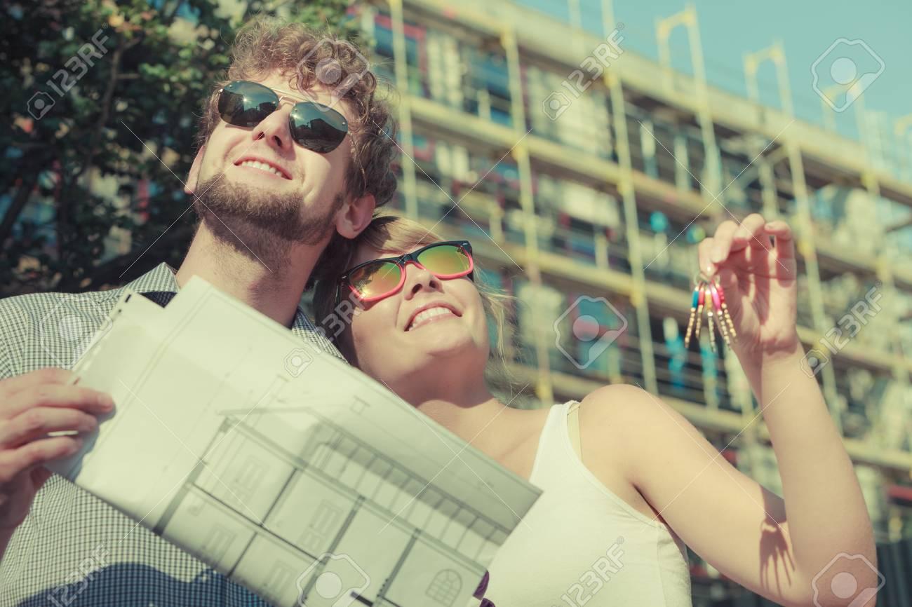 immobilier et le concept de la famille jeune couple sur le devant de la nouvelle grande maison moderne avec le projet de schma directeur et la cl de