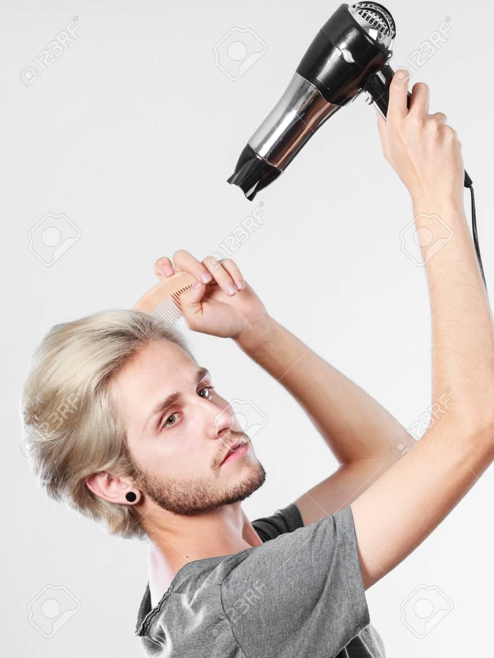 髪型とファッション。外観を変更する新しいアイデアを若いトレンディな男性ヘアスタイリスト床屋。ドライヤー髪を保持している金髪の男と櫛の新しいヘアスタイルを作成します。