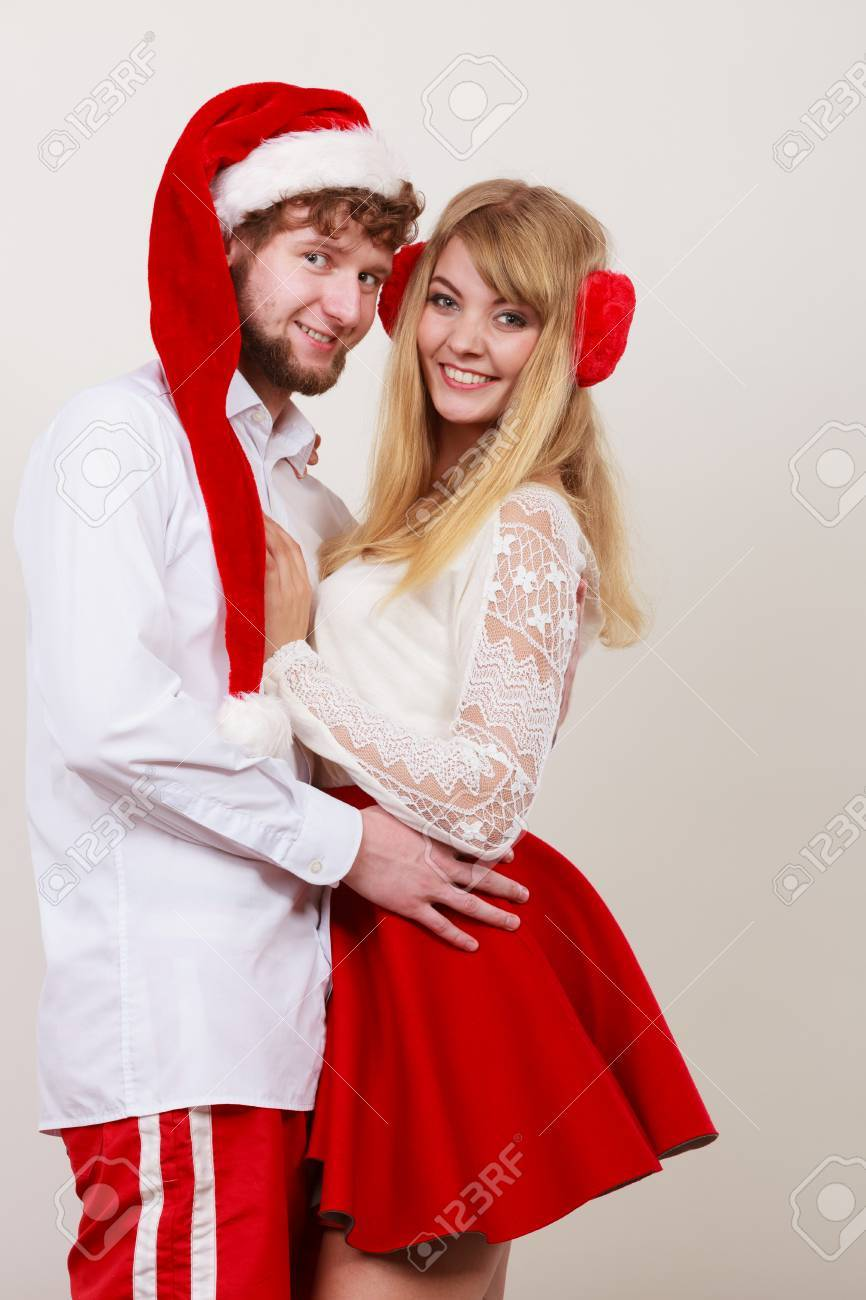 happy smiling cute couple pretty woman and man in santa claus hat christmas xmas