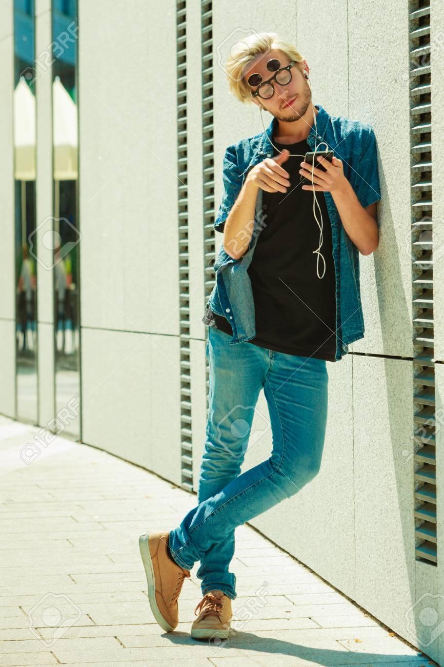 Moda de los hombres, tecnología, concepto de ropa de estilo urbano. Hipster hombre de pie en la calle de la ciudad vistiendo traje de vaqueros y gafas