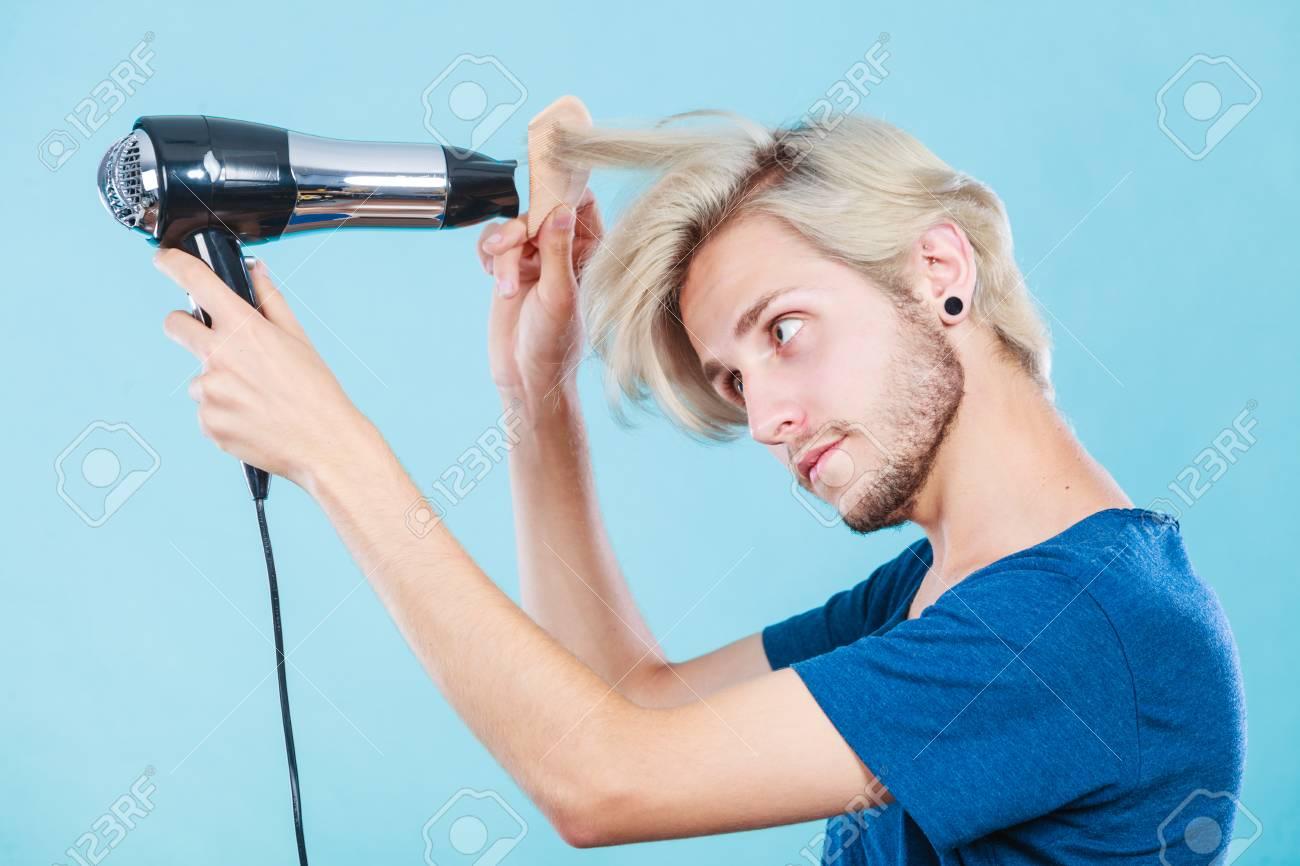 Le Style Et La Mode Jeune Coiffeur Male Branche Coiffeur Avec Une Nouvelle Idee De Changement De Look Homme Blonde Tenant Un Seche Cheveux Et Un Peigne Creant Nouvelle Coiffure Sur Le Bleu