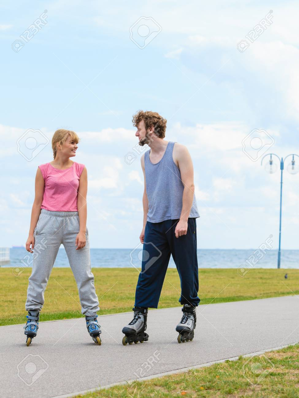 Active holidays, exercises, relationship concept. Woman and man wearing rollerskates standing and looking at each other - 81187328
