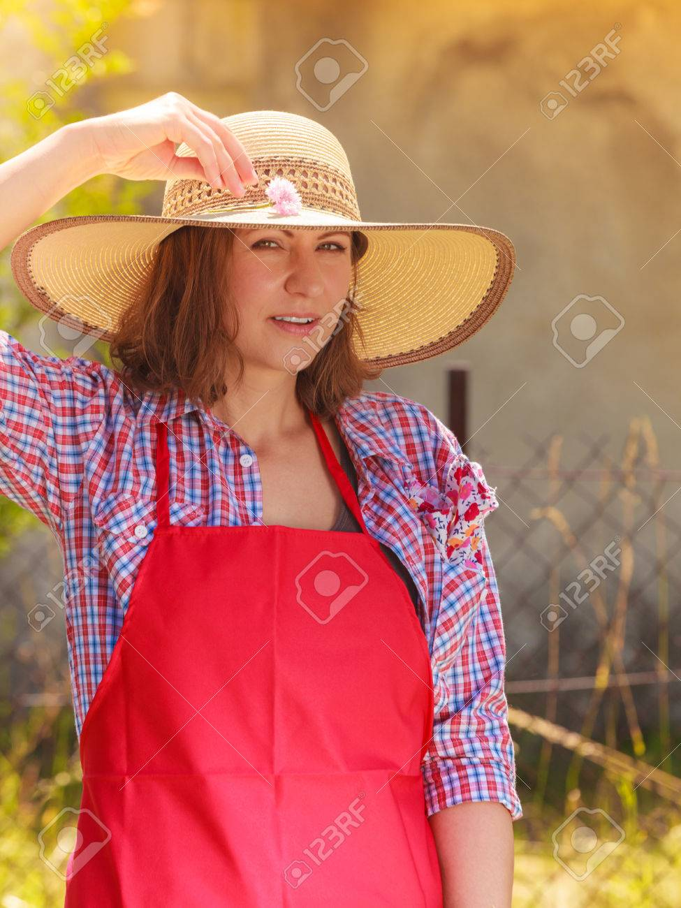 8f5d8c8a678bd Portrait of mature smiling woman wearing big straw hat in garden Stock  Photo - 84436021