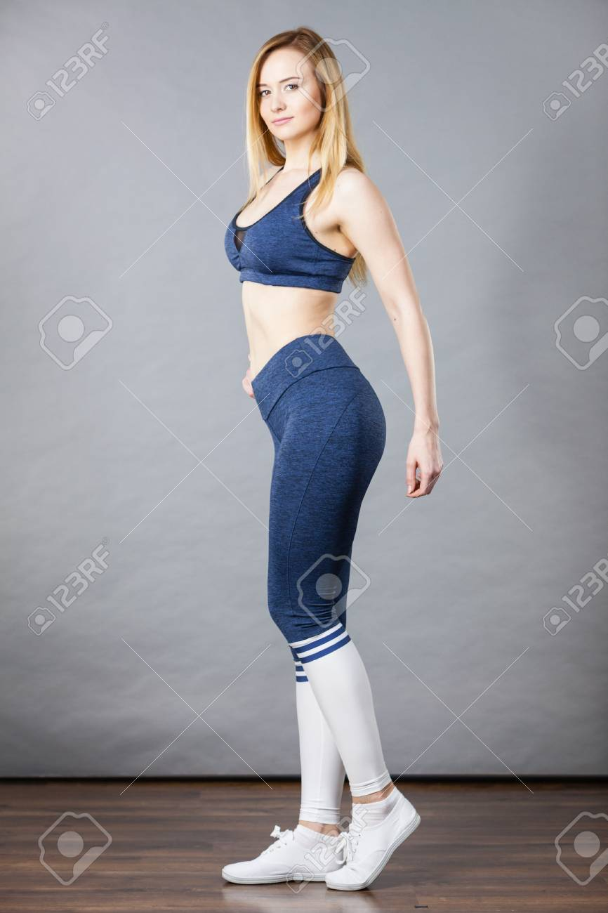 ee03fa0a9e Stock Photo - Woman wearing sporty workout outfit, blue sport bra, leggings,  socks and trainers. Indoor shot on grey background.