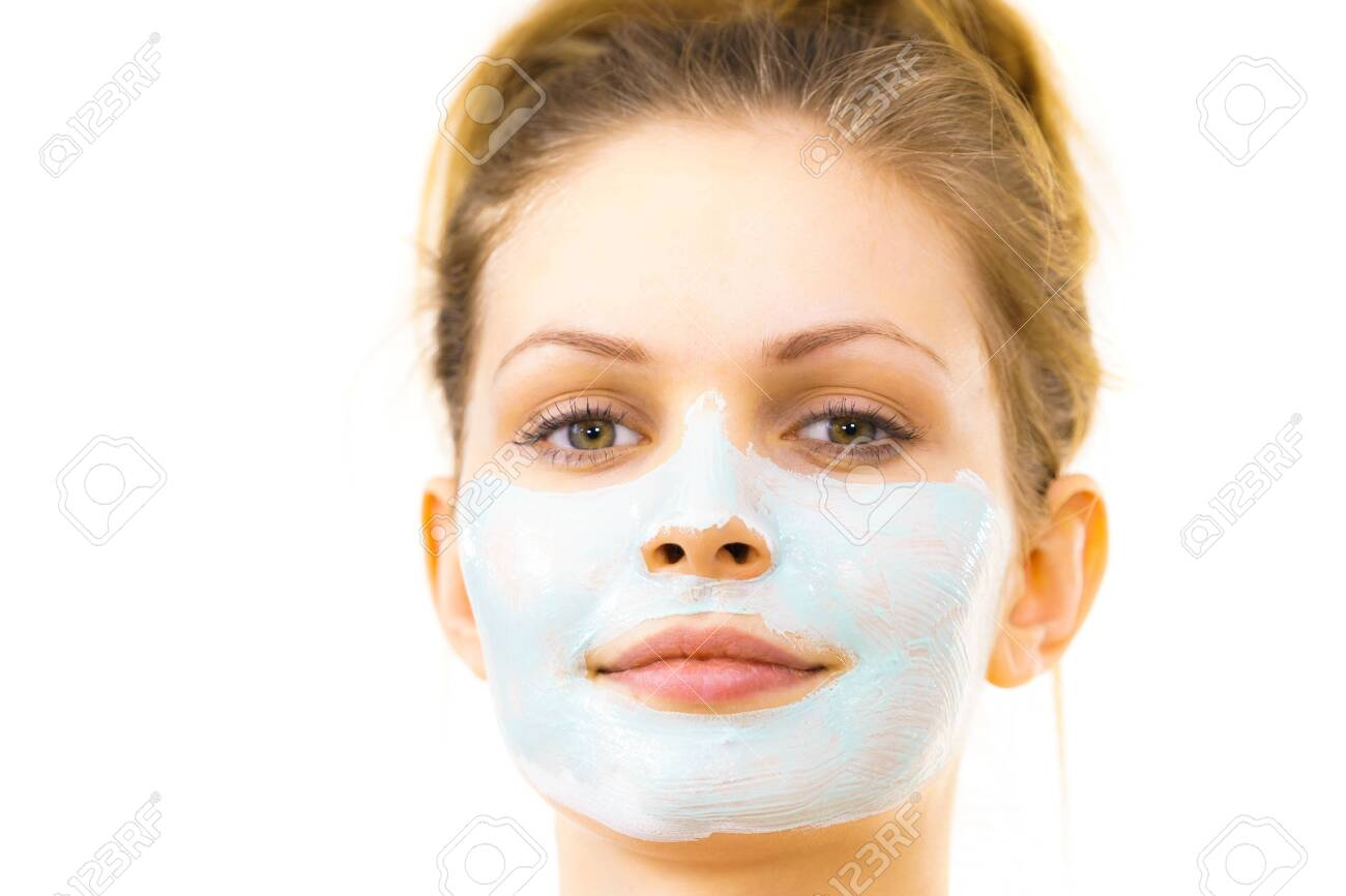 Young woman applying green mud mask to face, on white. Teen girl taking care of oily skin, purifying the pores. Beauty treatment. Skincare. - 121855357