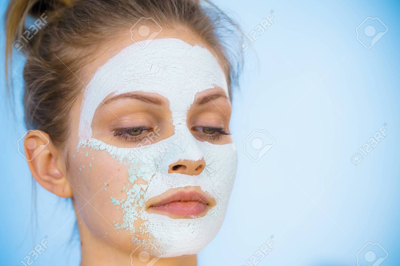 Young woman with white dried mud mask on face being removing cosmetic. Teen girl taking care of oily skin. Beauty treatment. Skincare. - 123358212