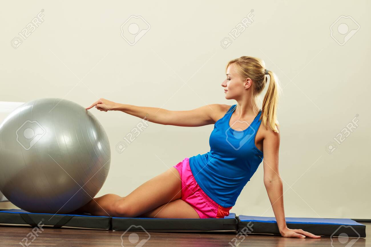 Sport, training, gym and lifestyle concept. Young attractive slim woman in sportswear doing fitness exercises with fit ball at home - 149346066