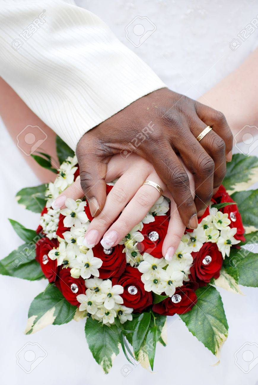 Wedding flowers and hands of a newly-married couple with wedding rings Stock Photo - 13896022