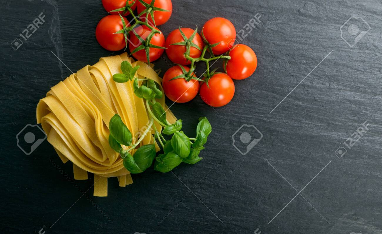 Raw yellow italian pasta pappardelle, fettuccine or tagliatelle close up. Egg homemade dry ribbon noodles, long rolled macaroni or uncooked spaghetti with tomatoes and basil top view - 124786987