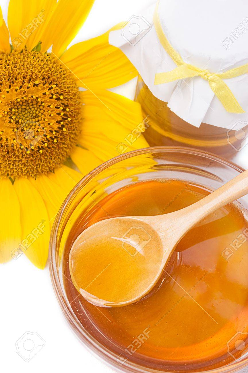 Honey in jar with wooden spoon and sunflower Stock Photo - 10117982