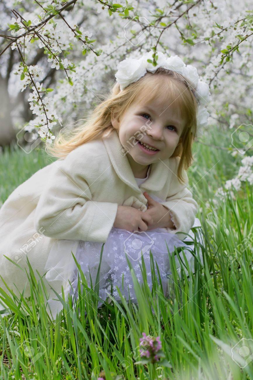 Happy smiling girl sitting among spring blossom garden Stock Photo - 19264572