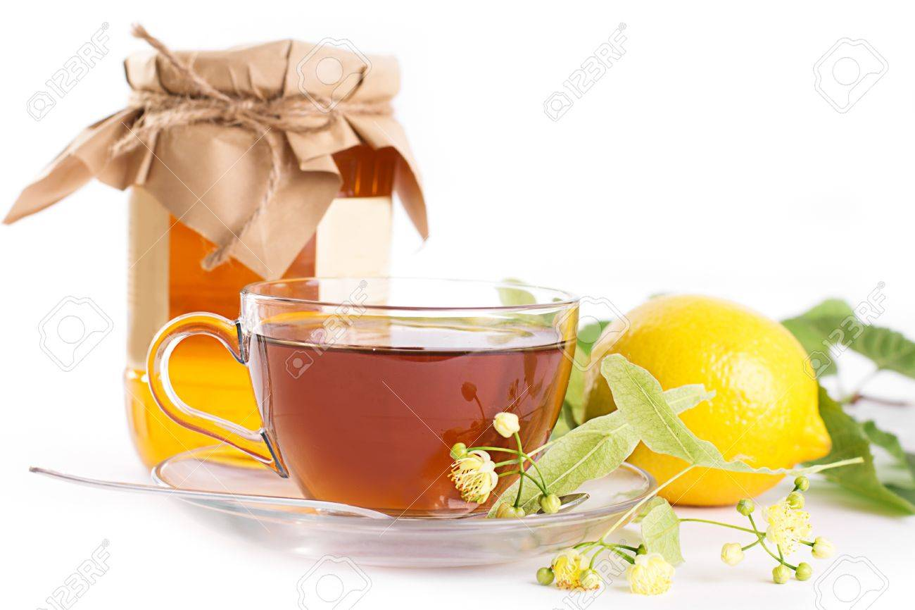 Lemon tea with linden honey jar and flowers over white Stock Photo - 20324293
