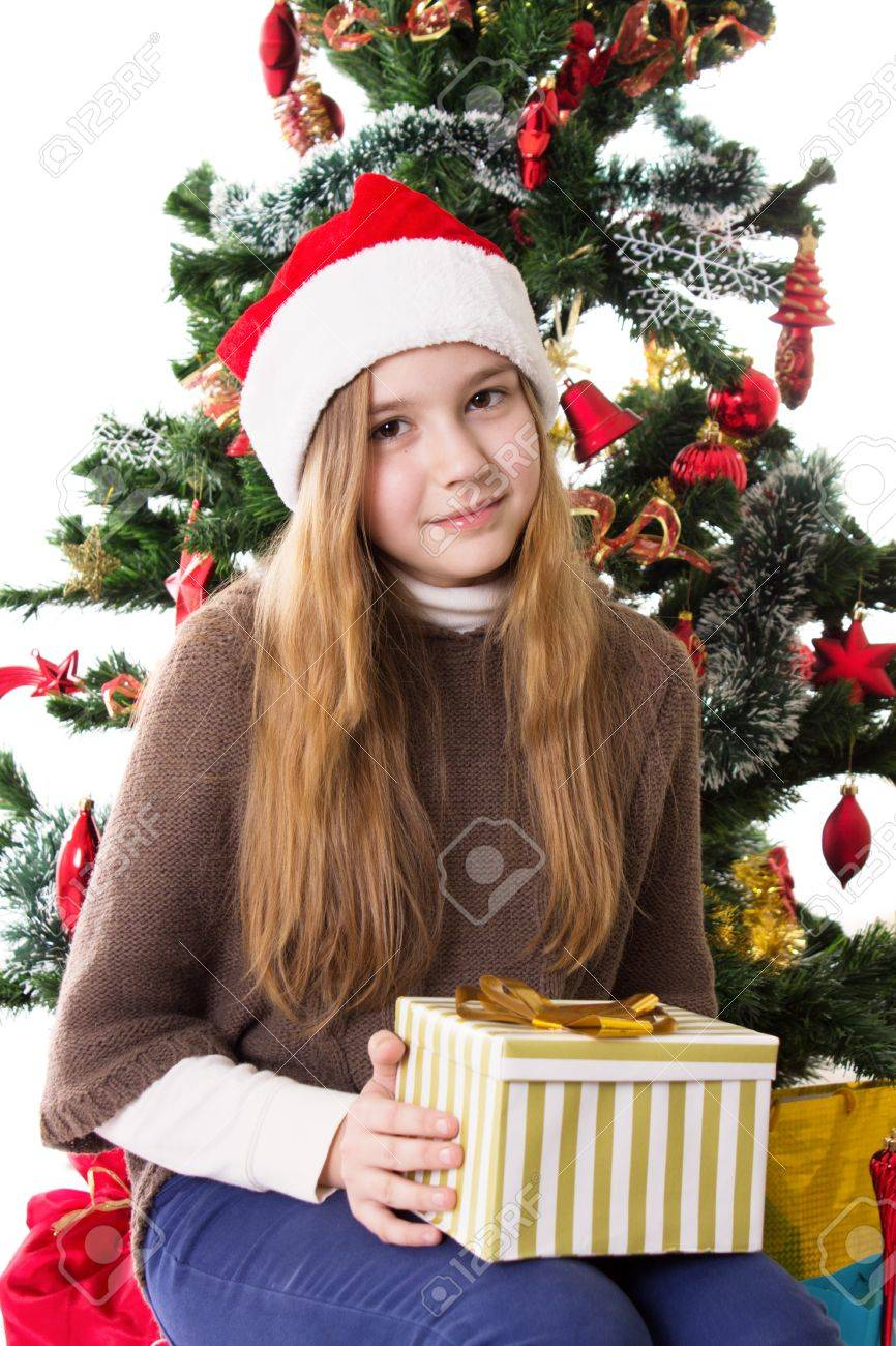 Cute Christmas Gifts For Teenage Girls.Cute Teenage Girl In Santa Hat With Present Under Christmas Tree