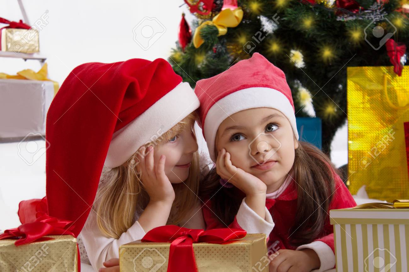 Two girls in Santa hats sharing secrets under Christmas tree Stock Photo - 24370586