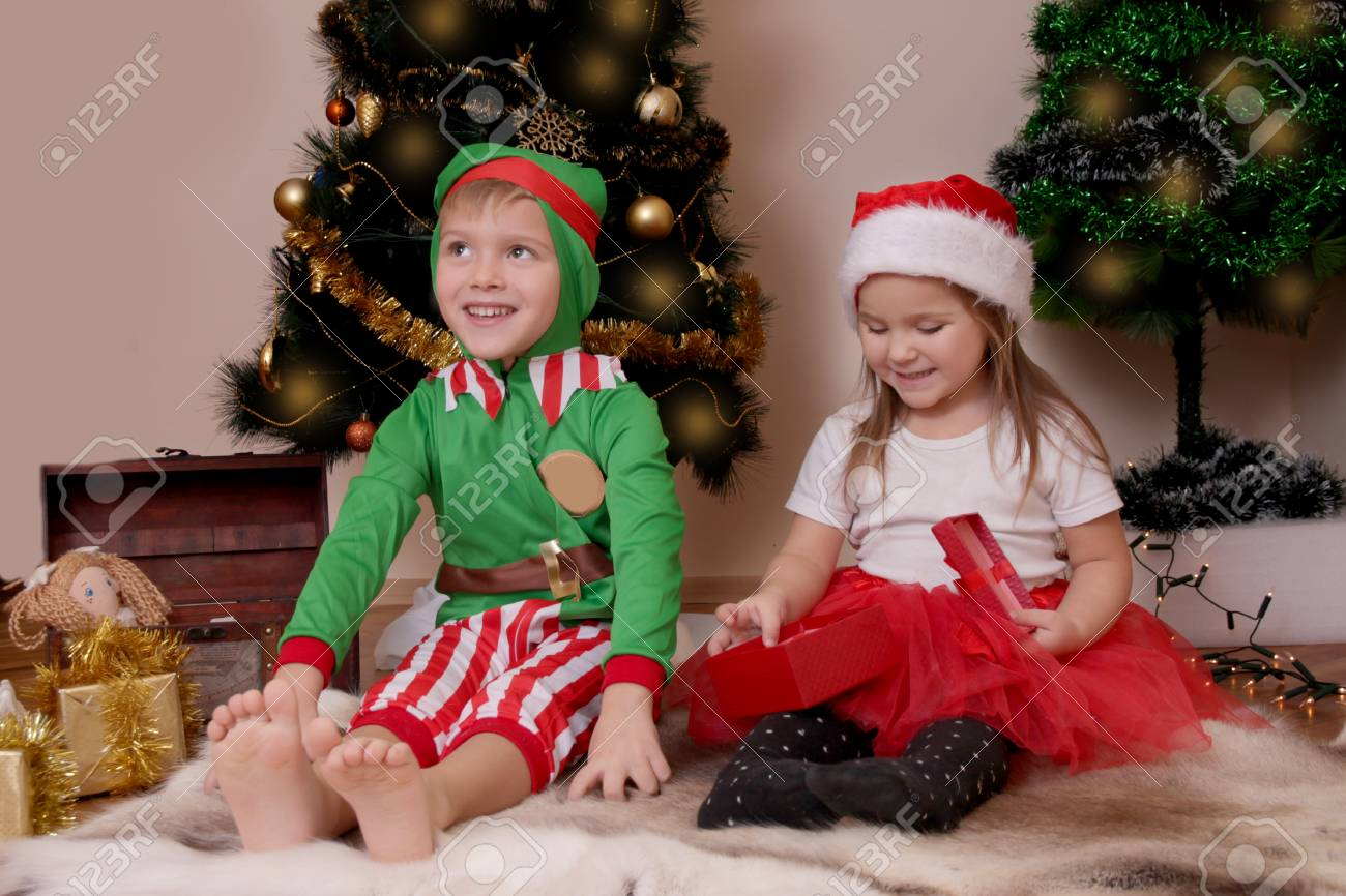 Two Happy Children In Costumes Opening Christmas Gifts Stock Photo ...