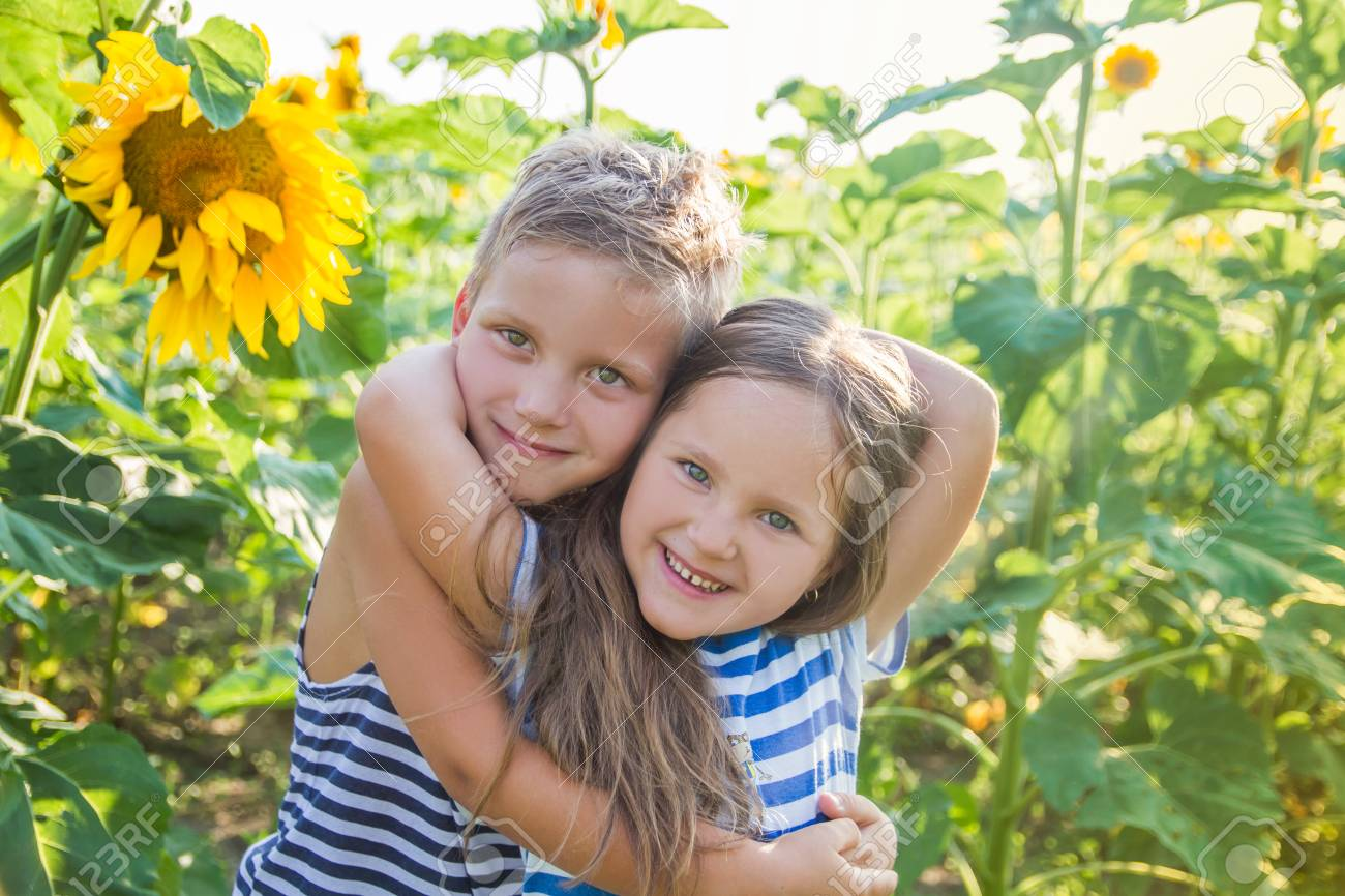 happy boy and girl hugging among sunflower field stock photo