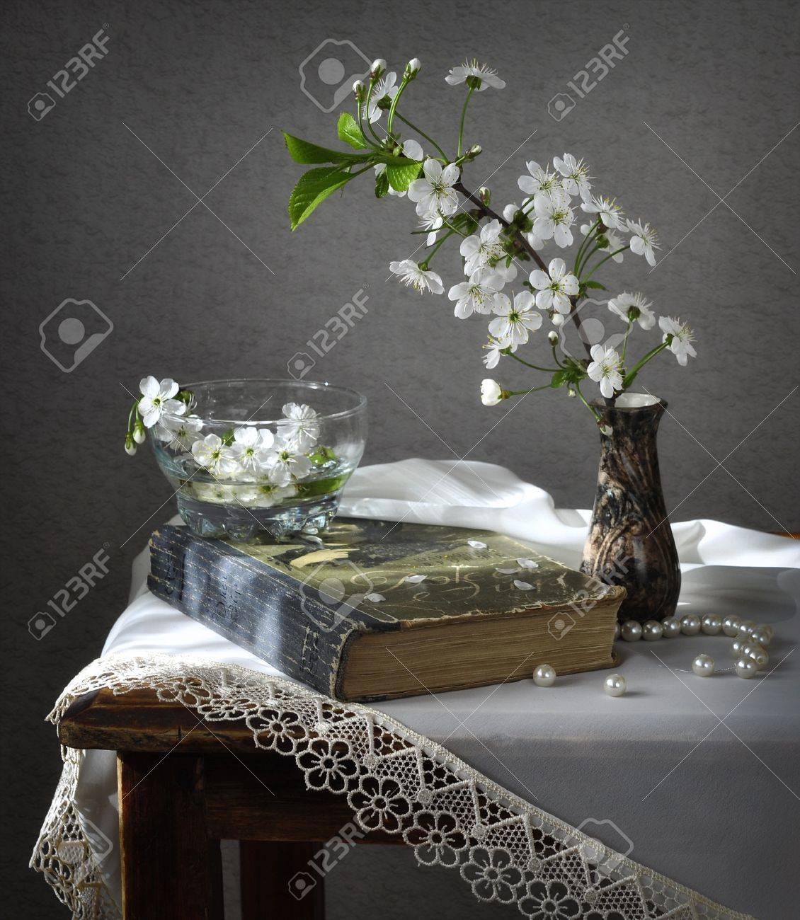 Still life with the book and the efflorescent cherries. Stock Photo - 9583164