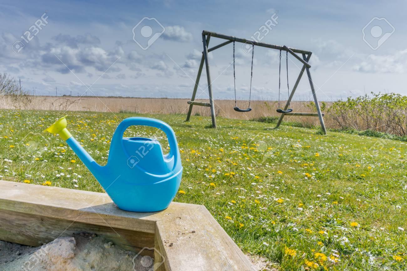 sandkasten im garten mit kindern bewässerung und eine schaukel im