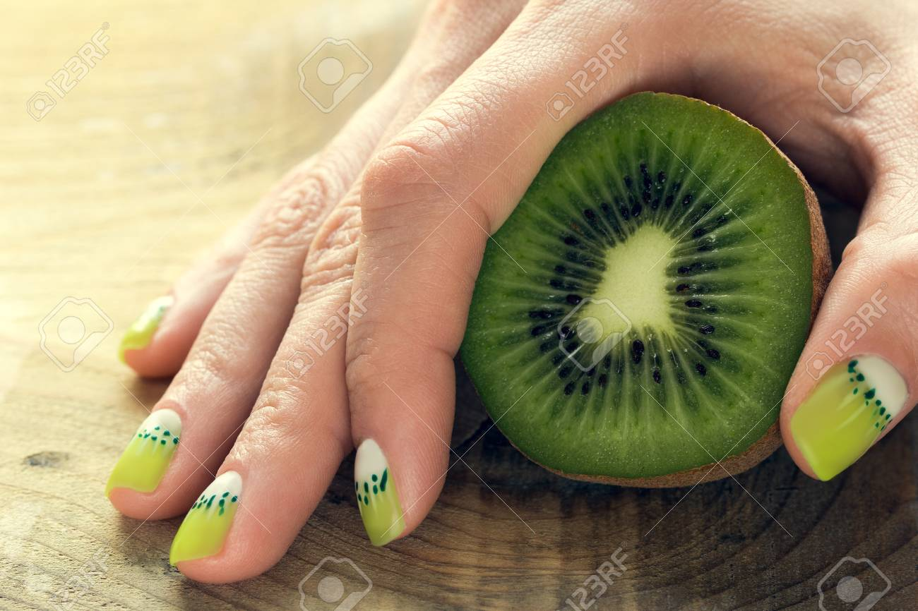Kiwi And Female Hand With Green And White Moon Nail Art Manicure