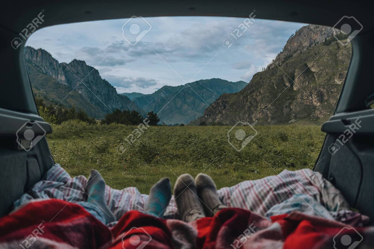 Summer landscape with mountains, the view from the car. Legs of resting people on nature. Sleeper in the car. Travelers are in the car and look at the mountains. - 117271949