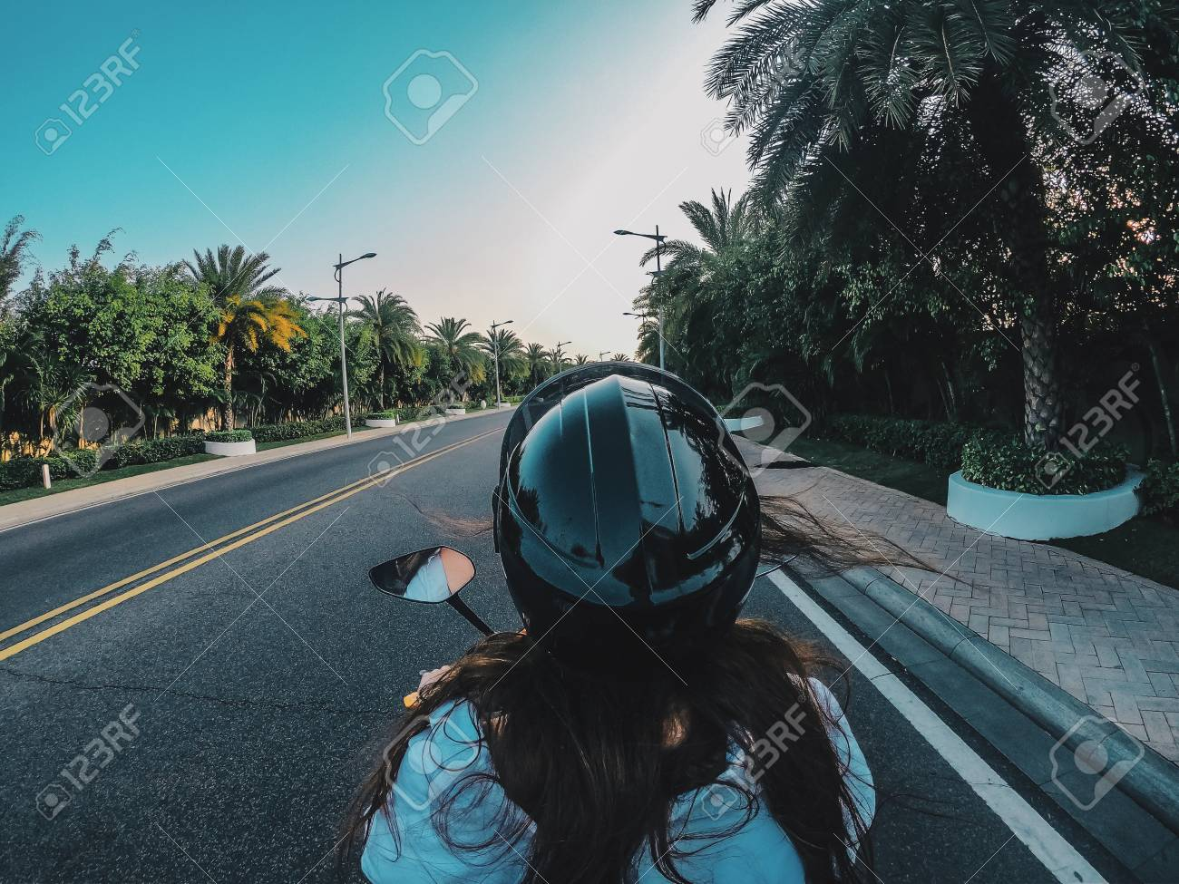 A girl in a black helmet is driving a motorcycle on a flat road in China. Traveler rides next to palm trees, trees grow along the road. - 126733325