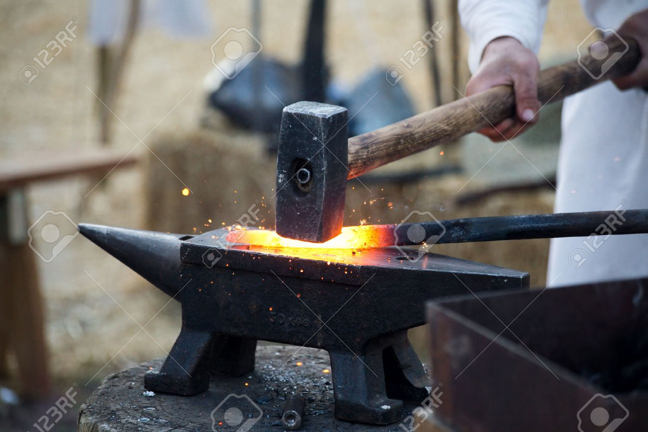 blacksmith working metal with hammer on the anvil in the forge - 29256584