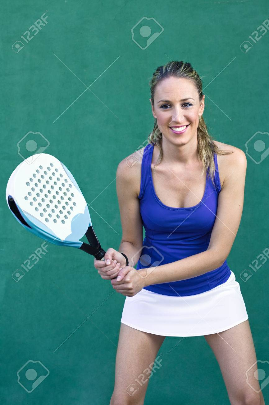 young woman playing paddleball tennis on paddle court wall green background - 32430514