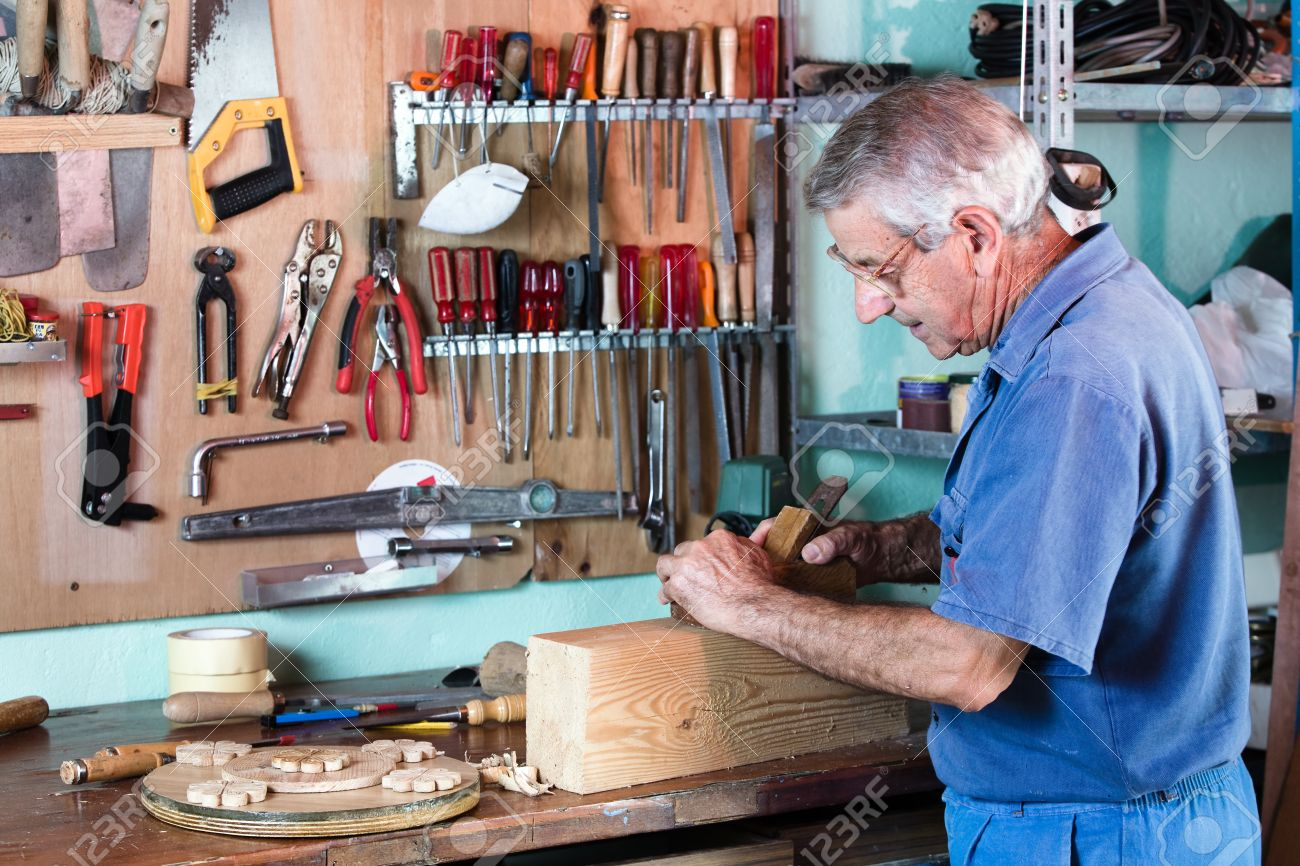 Cabinetmaker Sanding A Piece Of Wood In His Workshop With Tools