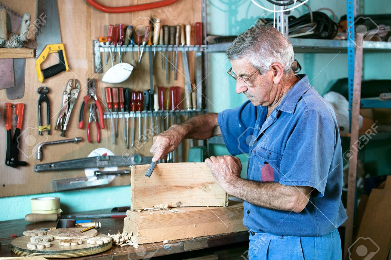 Work Of A Carpenter Sanding A Piece Of Wood In The Workshop Of ...