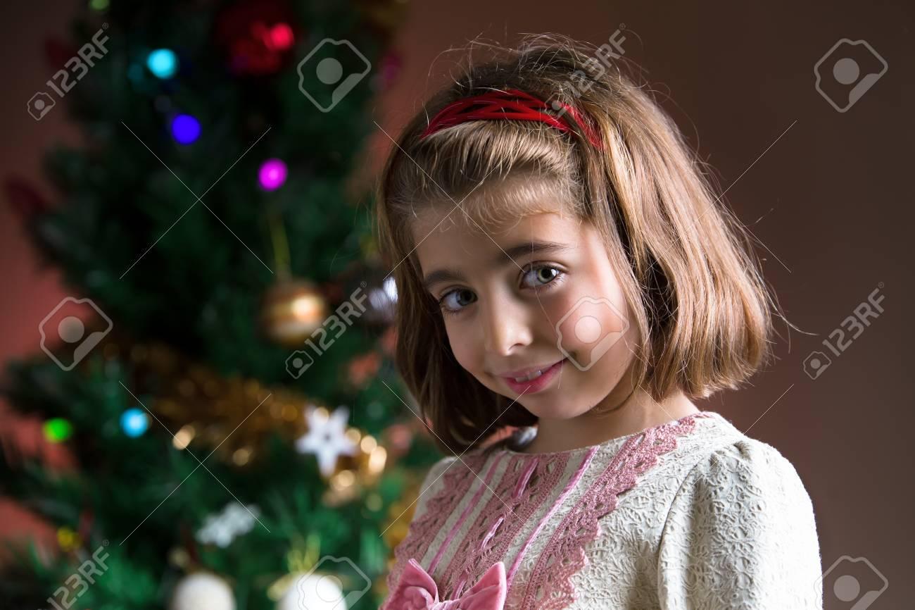 Porträt Von Cute Mädchen Blick In Die Kamera Und Die Weihnachtsbaum ...
