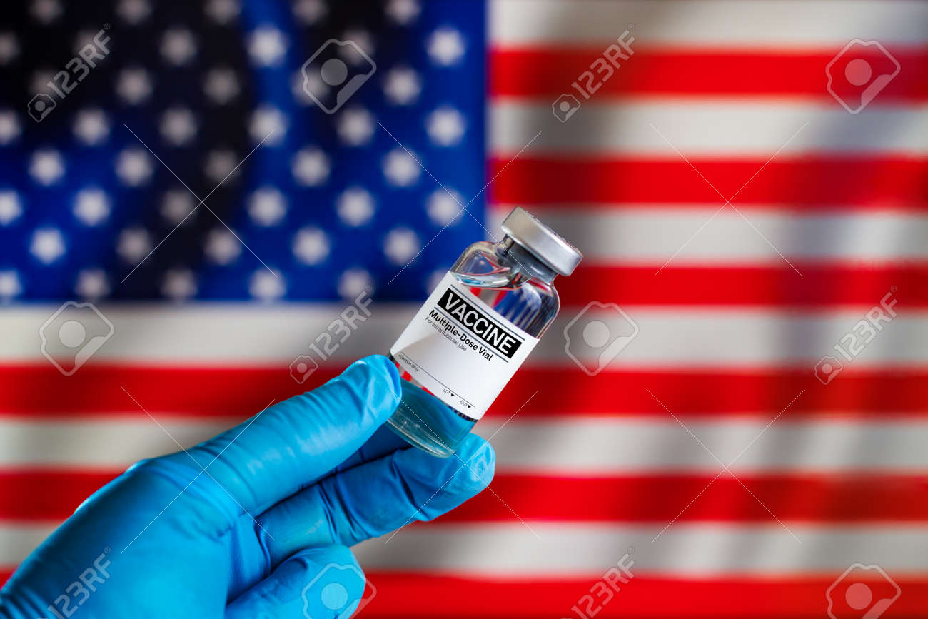 Doctor with a vial with doses of the vaccine in front of the US flag. Preparation of vaccine injection for the annual vaccination plan against diseases in the USA. - 167634740