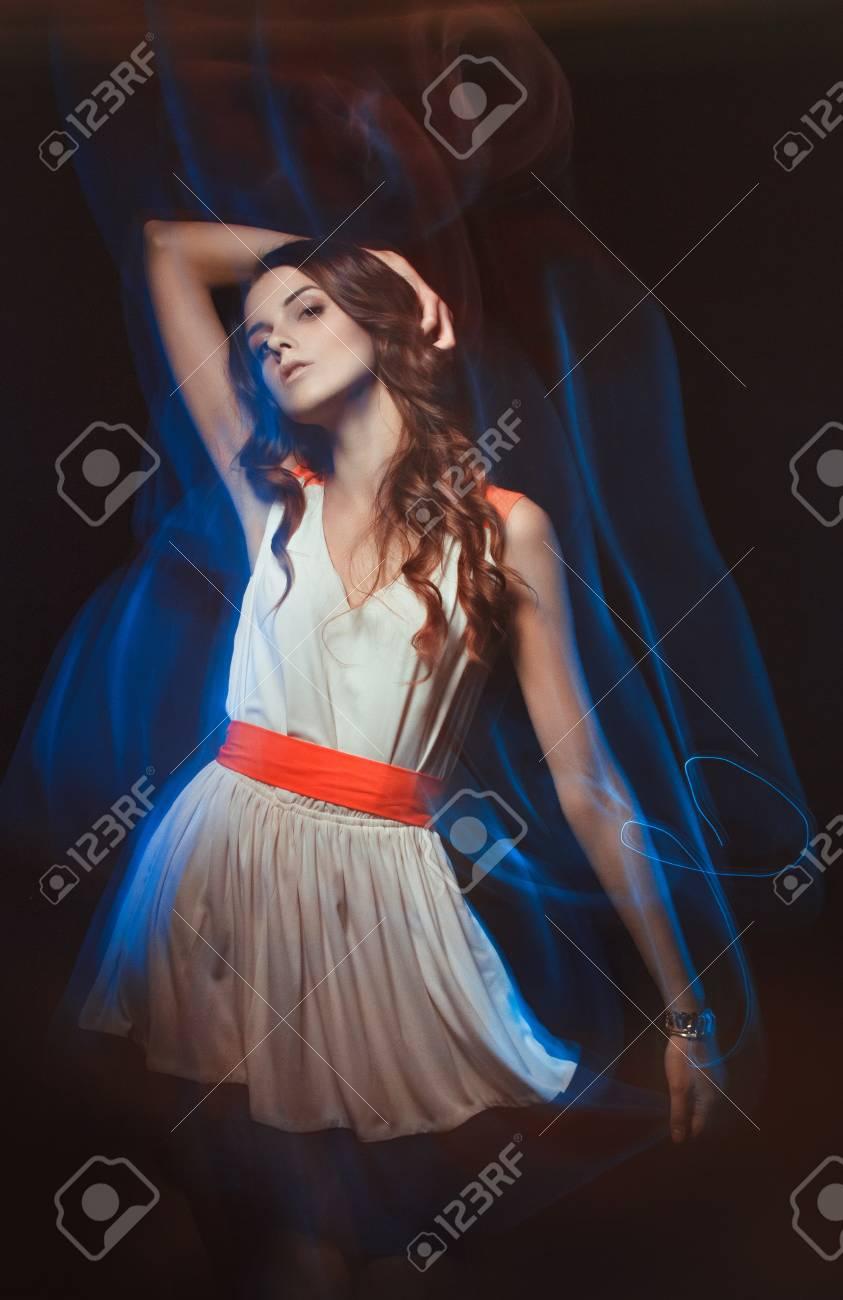 f79d328e92 Ritratto di arte vaga di colore di una ragazza su uno sfondo scuro. Moda  donna con bel trucco e un vestito estivo leggero. Sensuale immagine tenera  di ...