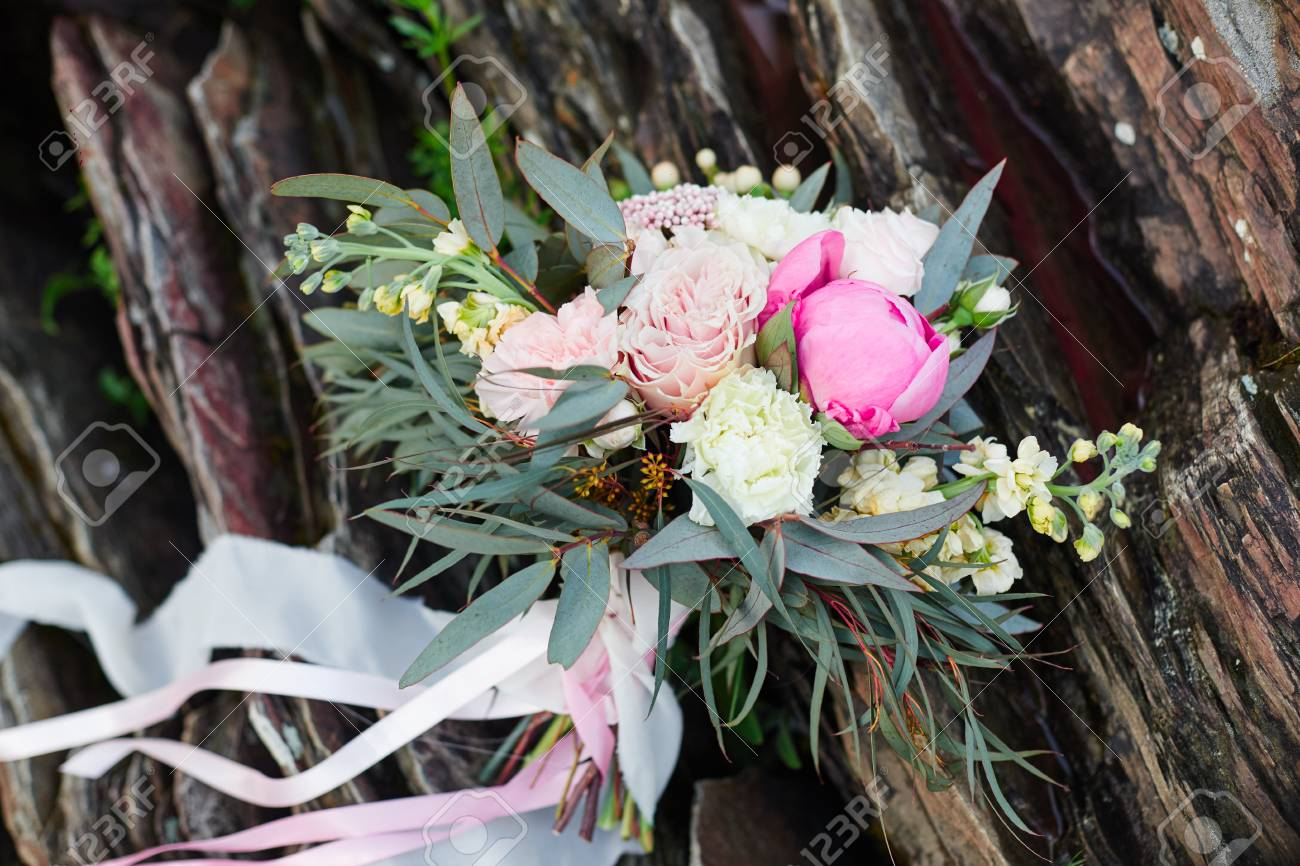 Beautiful bridal bouquet lying on the stones a bouquet for the beautiful bridal bouquet lying on the stones a bouquet for the girls wedding ceremony izmirmasajfo Image collections
