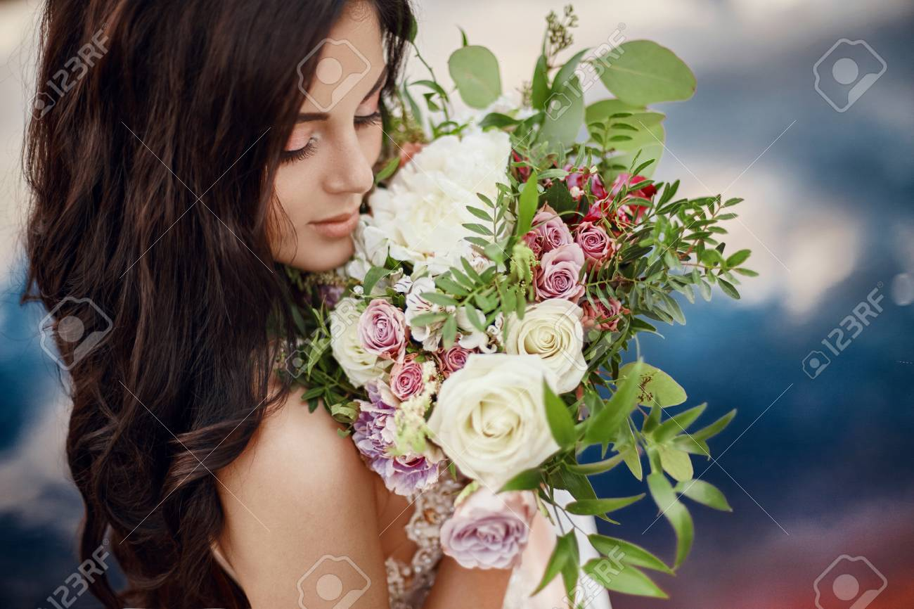Portrait Woman With Blue Eyes And Bouquet Of Flowers In Her Hands