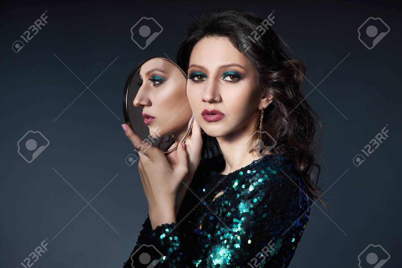 Beauty portrait of a woman with beautiful evening makeup and a mirror in her hands, a brunette girl in a shiny evening dress with sequins. Natural cosmetics for face - 139999291