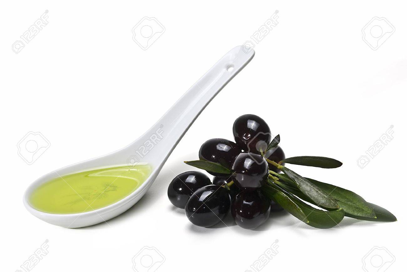 A spoon with olive oil and some black olives isolated on a white background. Stock Photo - 8759327