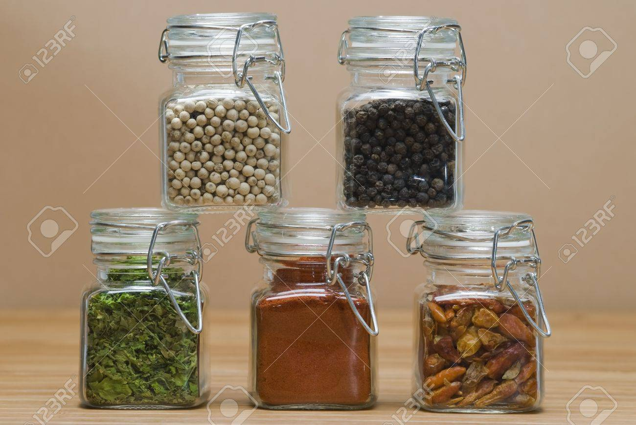 Some jars with spices on a wooden surface. Stock Photo - 9319487